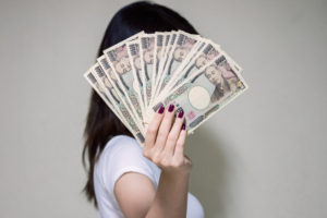 お金で顔を隠す女性