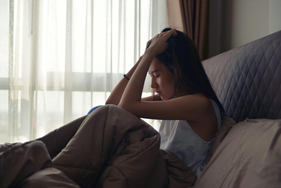 ベッドで悩む女性
